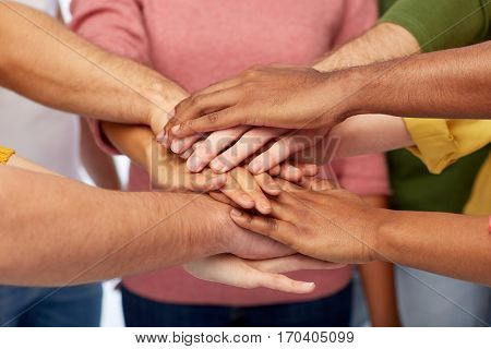 friendship, international, teamwork and people concept - close up of hands on top of each other