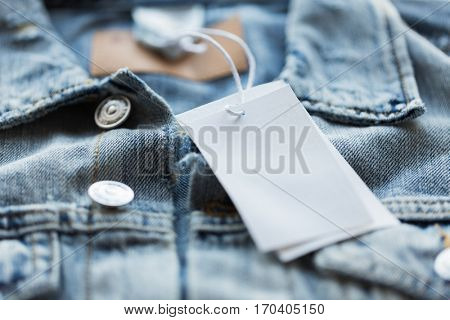 clothes, wear and fashion concept - close up of denim jacket with white price tag