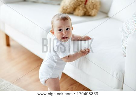 childhood, babyhood, emotions and people concept - happy little baby boy or girl at home