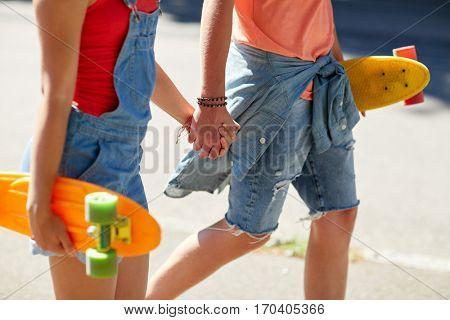 summer, relations, extreme sport and people concept - close up of happy teenage couple with short modern cruiser skateboards walking along city street