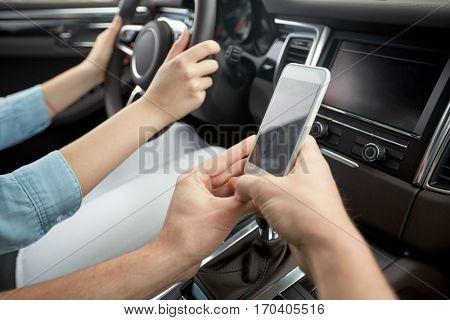 road trip, travel, destination technology and people concept - happy man and woman with navigator on smartphone driving in car