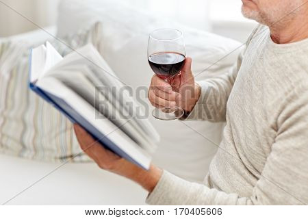 age, leisure and people concept - close up of senior man with wine glass reading book at home