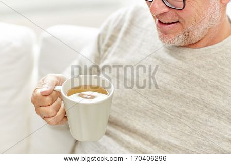 old age, drink and people concept - close up of happy senior man with cup of tea at home