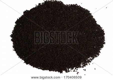 Heap of black tea scattered on the white surface