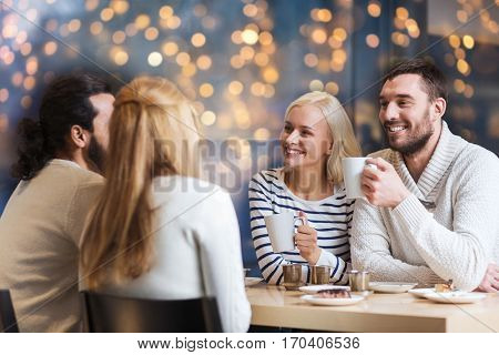 people, leisure, communication and friendship concept - happy friends meeting and drinking tea or coffee at cafe over holidays lights
