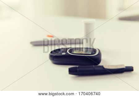 medicine, diabetes and health care concept - close up of glucometer and blood sugar test stick on table