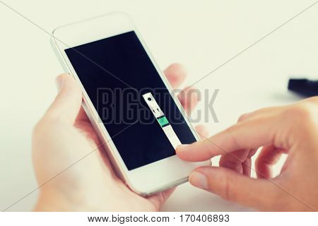 medicine, diabetes, glycemia, health care and people concept - close up of woman hands with smartphone and test stripe checking blood sugar level by glucometer application at home