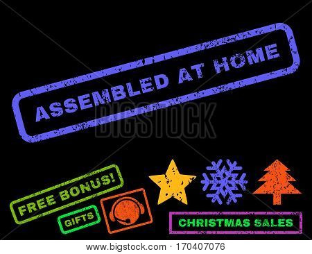 Assembled At Home text rubber seal stamp watermark with additional bonus new year symbols. Caption inside rectangular banner with grunge design and scratched texture.