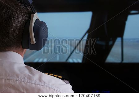 Close up of captain's epaulettes and headphones in the cockipt of commercial airplane