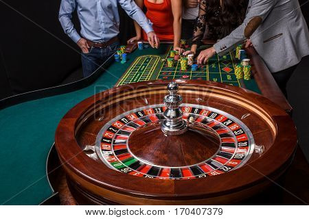 Group of young people behind roulette table on black background. Young people are betting in the game. close-up