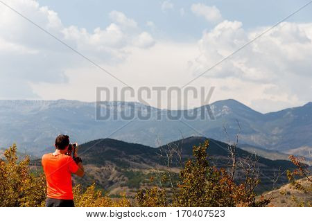 Man photographing scenic mountain landscape in day
