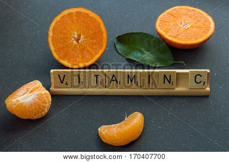 Oranges on a table. Vitamin c written in scrabble letters