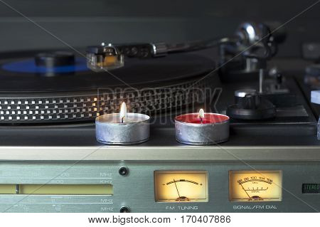 Front shot of a retro vinyl player with candles in a center of shot