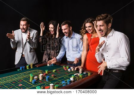 Group of young people behind roulette table on black background. Young people made bets in the game and wait for the result. Bright emotions