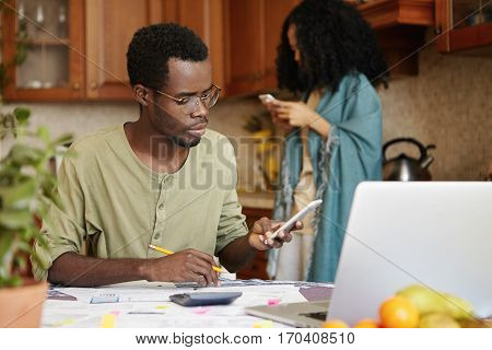 Young Dark-skinned Husband Sitting At Kitchen Table With Papers, Calculator And Laptop, Doing Paperw