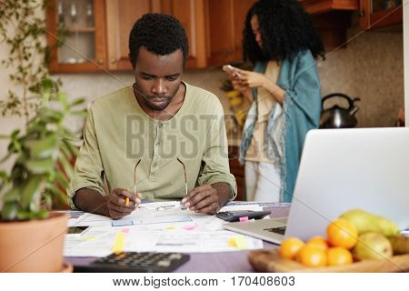 African Man With Glasses And Pencil In His Hands Looking In Frustration At Papers In Front Of Him Wh