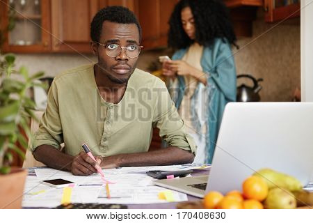 Young African Male Feeling Stressed Paying Bills Online, Calculating Gas And Electricity Expenses, S