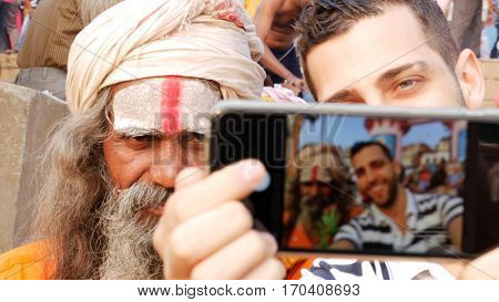 Tourist taking a selfie with Sadhu Holy Man in India