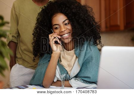 Happy African Housewife Holding Mobile Phone And Talking To Her Friend, Sitting At Kitchen Table, Ma