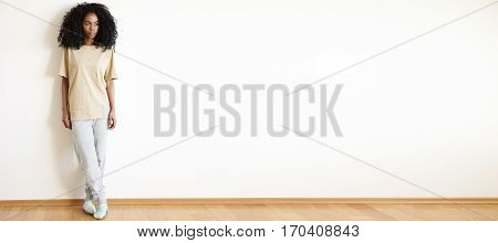 Attractive Stylish Dark-skinned Female Model With Afro Hairstyle Looking Away While Posing Indoors A