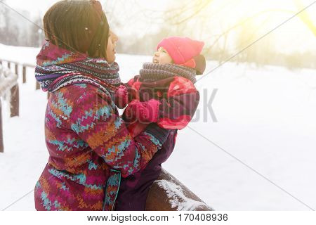 Brunette with daughter relaxing in winter park at afternoon