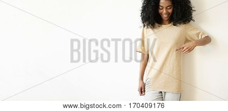 Indoor Shot Of Beautiful Young African Woman With Cute Smile Looking Down And Pointing At Copy Space