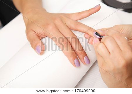 Manicure. Beautiful manicured woman's nails with violet nail polish on soft white towel.