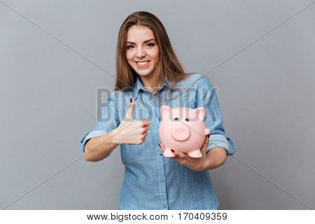 Smiling Woman in shirt holding moneybox in hand and showing thumb up. Isolated gray background