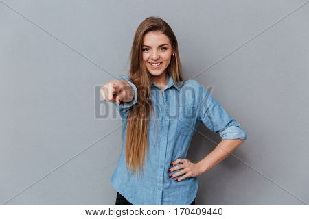 Smiling Woman in shirt pointing at camera with arm at hip. Isolated gray background