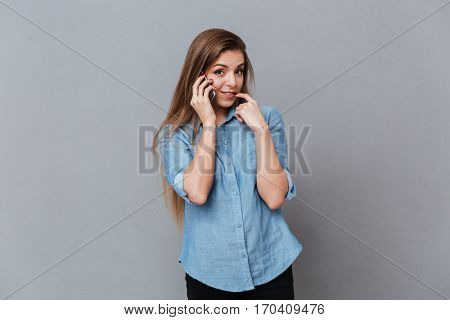 Shy Woman in shirt talking on phone with finger in mouth. Isolated gray background