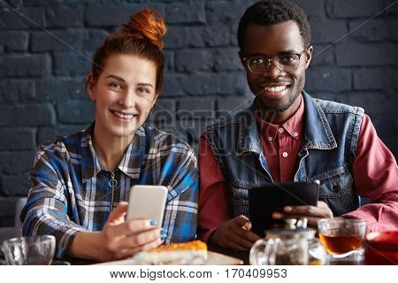 Young Modern People With Electronic Devices Having Fun During Coffee Break Indoors At Cafe. Redhead