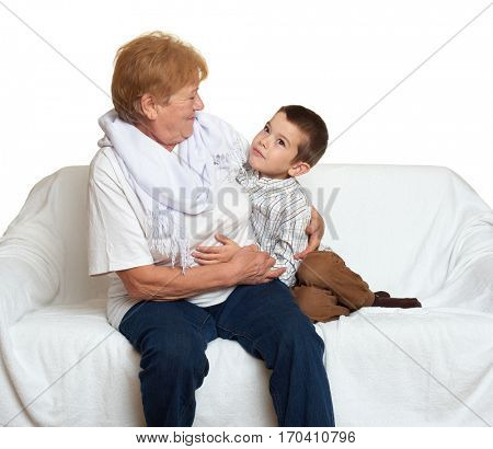 Family portrait on white background, happy people sit on sofa. Grandmother with grandchild.