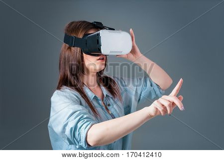 Emotional young woman using a VR headset and experiencing virtual reality on grey background. A woman dressed in a denim shirt