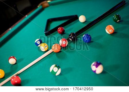 billiard table with billiard balls, cue and billiard triangle