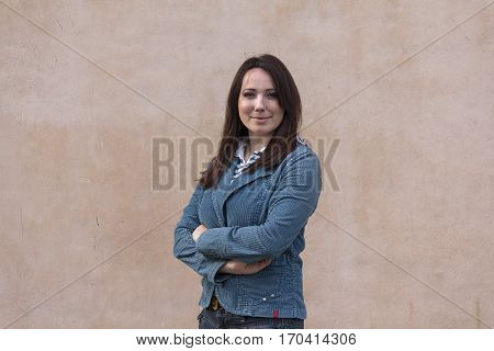 Beautiful woman in a blue jacket on the background wall. People