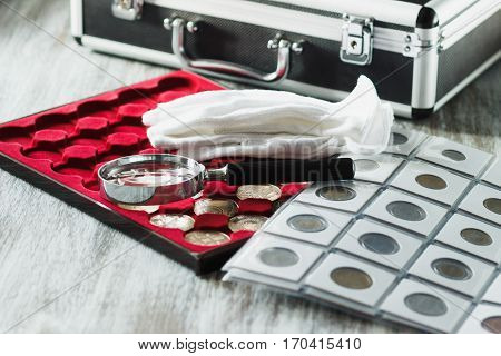 Different Collector's Coins With A Magnifying Glass And Gloves