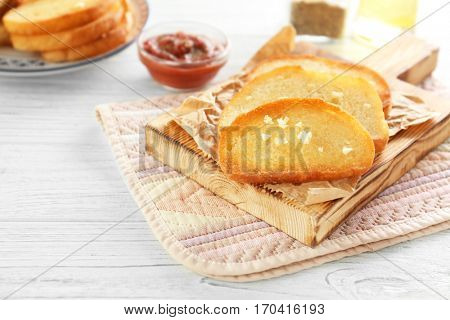 Tasty garlic French bread slices on wooden table