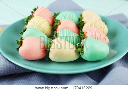 Plate of strawberries covered with colorful chocolate icing on napkin, closeup