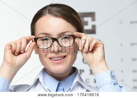 Young woman with spectacles on eyesight test chart background