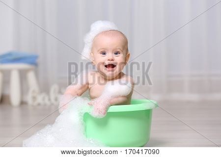 Cute baby washing in plastic basin at home