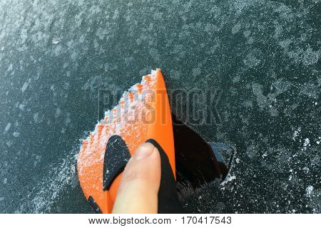 hand with orange scraper is scraping a frozen car windshield in the morning
