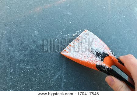 hand scraping a frozen car windshield in the morning