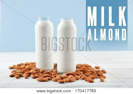 Food substitute concept. Glass bottles with almond milk on white wooden table