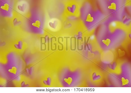 hearts pink-yellow on blurred pink-orange-yellow background bokeh. Arrangement on Valentine's Day. Bright collage. For design.