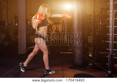 Young Girl Doing Boxing Workout In The Gym. Female Fighter Smash Punching Bag.
