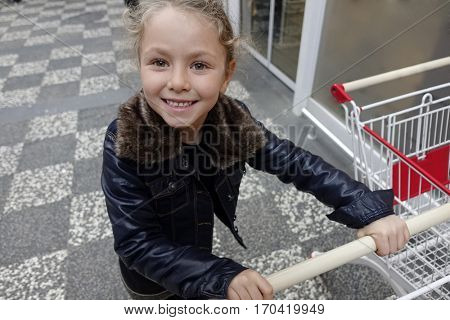 Cute little girl happy with shopping cart.