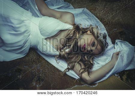 Ocean and sea, Greek vestal virgin, beautiful blond woman in white silk dress in a romantic or fantasy scene. Jewelry headdress made in silver