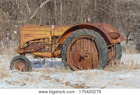 an abandoned tractor along the roadside next to a grove of trees.