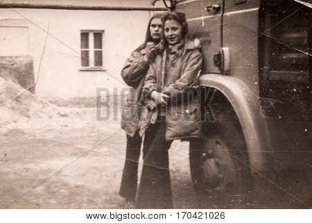 PIESZYCE, POLAND, CIRCA 1970's: Vintage photo of two girls in front of military lorry