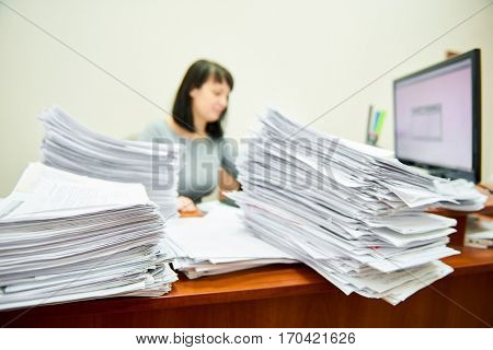 Female worker accountant with lots of paper documents